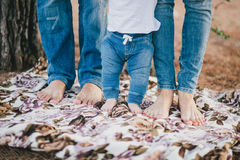 Mother, father and baby feet wearing jeans Royalty Free Stock Images