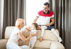 Mother, father, baby girl and daughter on the couch in the livin Stock Photography