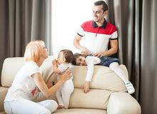 Mother, father, baby girl and daughter on the couch in the livin Royalty Free Stock Photos