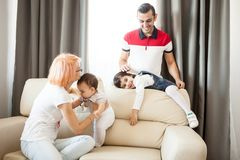 Mother, father, baby girl and daughter on the couch in the livin Royalty Free Stock Photography
