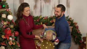 Mother, father and a baby have a fun in the room with christmas decoration. Dad and mom playing with child, throws him. Up holding in arms. Happy family stock footage