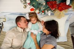 Mother, father and baby having fun in bedroom. People relaxing at home. Winter holiday Xmas and New Year concept. stock images