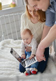 Mother ,father with baby and laptop sitting on bed at home Stock Photography
