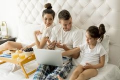 Young familly on the bed Royalty Free Stock Images