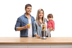 Mother, father and a baby posing behind a wooden counter with fruits in a blender. Isolated on white background stock images