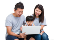 Mother, father and baby son looking at laptop computer Royalty Free Stock Photography