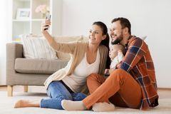 Mother and father with baby taking selfie at home Stock Image