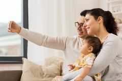 Mother and father with baby taking selfie at home. Family, technology, parenthood and people concept - happy mother and father with baby daughter taking selfie Royalty Free Stock Photos