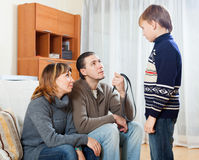Mother and  father with belt berating  boy Royalty Free Stock Photos