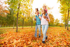 Mother and father carry little daughters in park Stock Photos