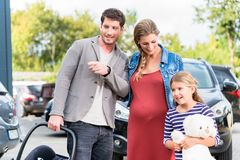 Mother, father, and child buying car at dealership. A new family auto royalty free stock image