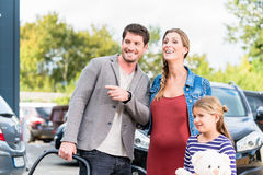 Mother, father, and child buying car at dealership Royalty Free Stock Image