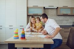 Mother, father and child draw together at the table. stock image