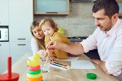 Mother, father and child draw together at the table. Development of children Stock Image