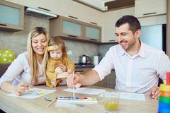 Mother, father and child draw together at the table. Development of children Royalty Free Stock Photo