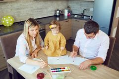 Mother, father and child draw together at the table. royalty free stock photos