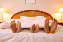Mother, father and child lie on soft bed Stock Photos