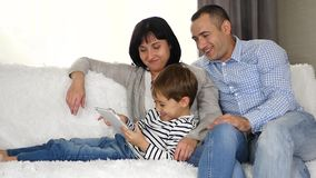 Mother, father and child use the tablet to watch a movie, play or use the Internet while sitting on the couch.Happy stock video footage