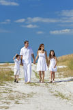 Mother, Father, Children Family Walking At Beach. A happy family of mother, father and two children, son and daughter, walking holding hands and having fun in Royalty Free Stock Photo