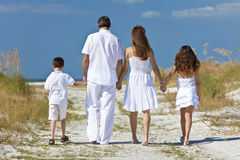 Mother, Father, Children Family Walking At Beach. Rear view of mother, father and two children, son and daughter, walking holding hands in the sand of a sunny Stock Image