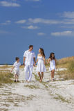 Mother, Father and Children Family Walking On Beach Stock Photo