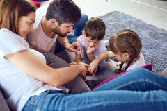 Mother, father and children play together. stock images