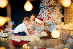 Mother and father with children playing at home on Christmas Day stock image
