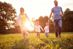 Mother and father with children running in nature. Mother and father with children running in green nature royalty free stock photography
