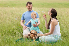 Mother and father and daughter blowing bubbles outdoors in summe Royalty Free Stock Images