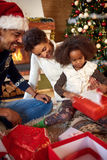 Mother, father and daughter in Christmas morning opening present Stock Photography