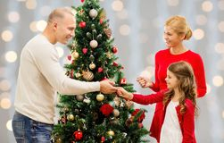 Mother, father and daughter at christmas tree stock photo