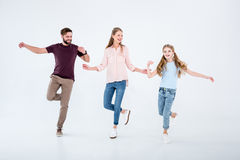Mother, father and daughter dancing together in studio Royalty Free Stock Image