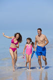 Mother, Father & Daughter Family Running on Beach. A happy family of mother, father and child, a daughter, running holding hands and having fun in the waves Royalty Free Stock Images