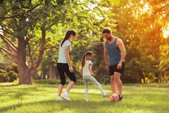 Family in the park playing football. They play a red soccer ball Stock Photo