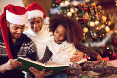 Mother, father and daughter read a book at fireplace on Christma Stock Photo