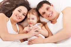 Mother, father and daughter resting on the white b Stock Photos