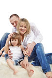Mother, father and daughter sit on carpet Stock Photos