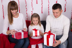 Mother, father and daughter sitting on sofa and opening christma Royalty Free Stock Image
