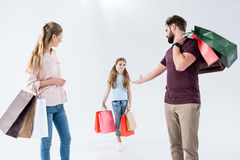 Mother, father and daughter standing with shopping bags royalty free stock photography
