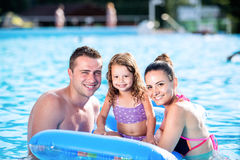 Mother, father and daughter in swimming pool. Sunny summer. Royalty Free Stock Photo