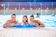 Mother, father and daughter in swimming pool. Sunny summer. Stock Photo