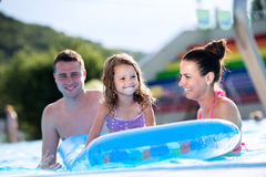 Mother, father and daughter in swimming pool. Sunny summer. Royalty Free Stock Photos