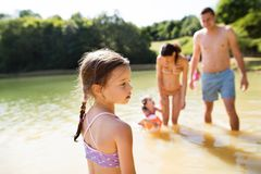Mother, father and daughters in the lake. Sunny summer. stock photo