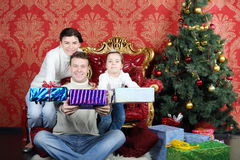 Mother, father and daugther give gifts near Christmas tree Royalty Free Stock Photos