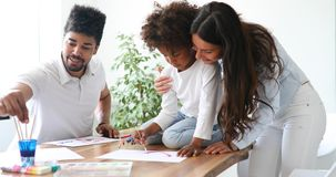 Mother and father drawing together with their child Royalty Free Stock Photo