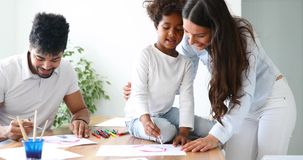 Mother and father drawing together with their child Royalty Free Stock Images