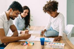 Mother and father drawing together with their child Stock Photography