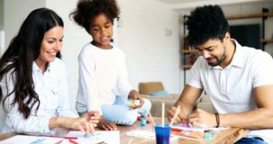Mother and father drawing together with their child Royalty Free Stock Photography