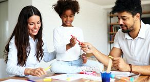 Mother and father drawing together with their child Stock Image