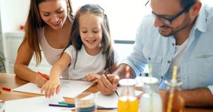 Mother and father drawing together with their child Stock Photos